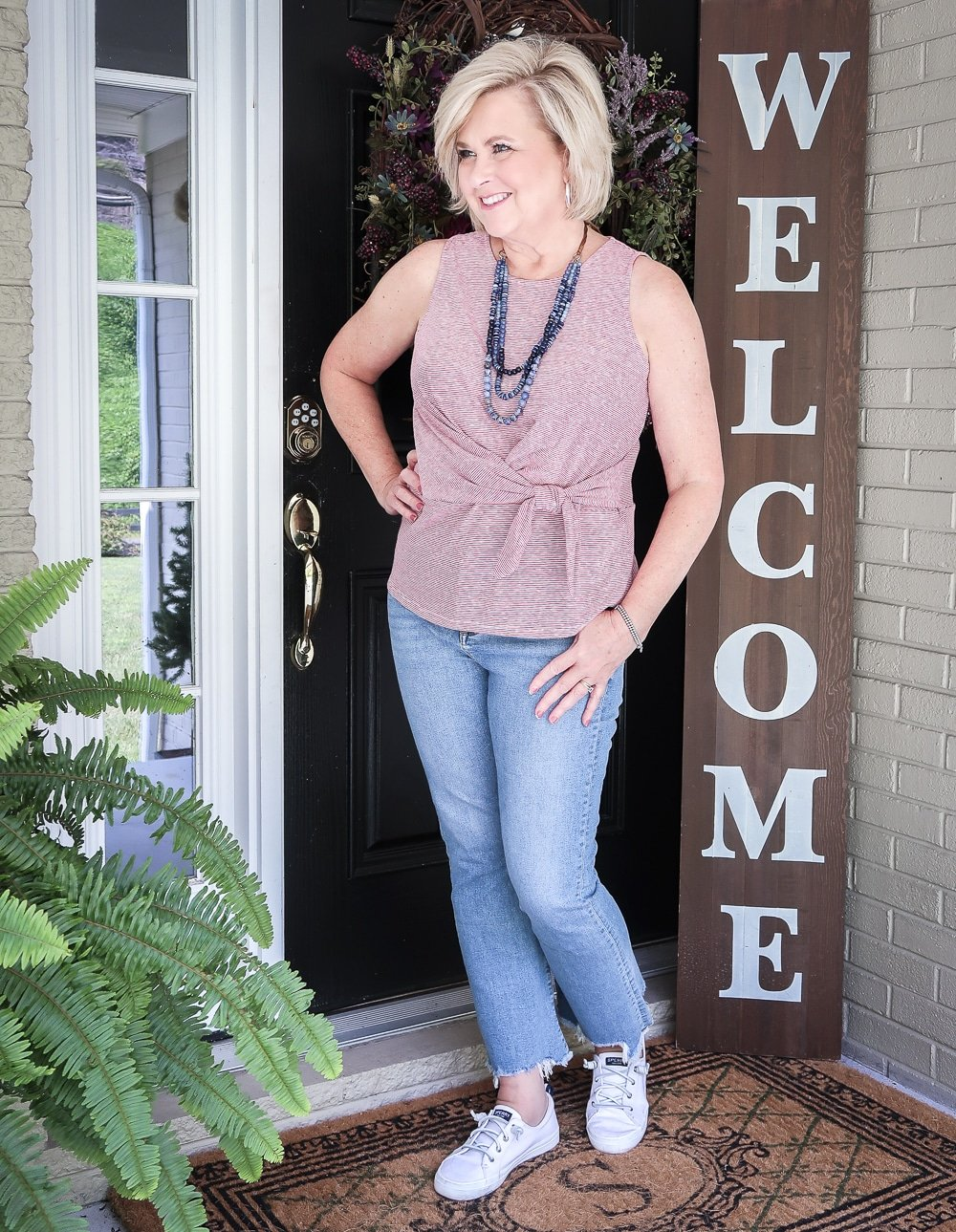 Fashion Blogger 50 Is Not Old is ready for looking to the side and wearing red white and blue top twist top, distressed jeans, and Sperry sneakers