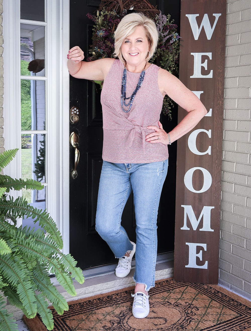 Fashion Blogger 50 Is Not Old is ready for celebrating Labor Day in her red white and blue top twist top, distressed jeans, and Sperry sneakers