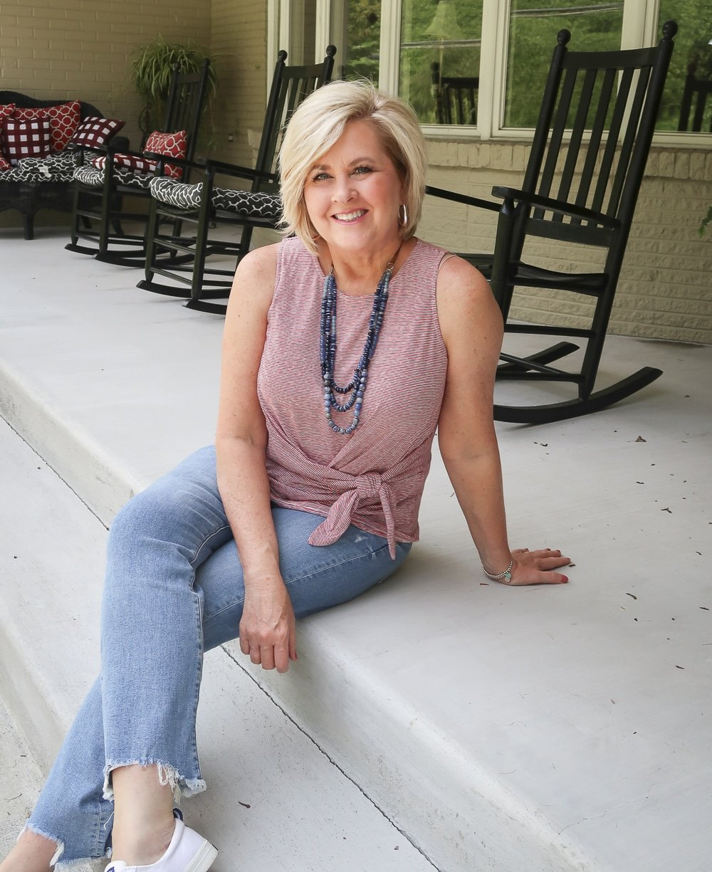 Fashion Blogger 50 Is Not Old is sitting on her porch in her red white and blue top twist top, distressed jeans, and Sperry sneakers