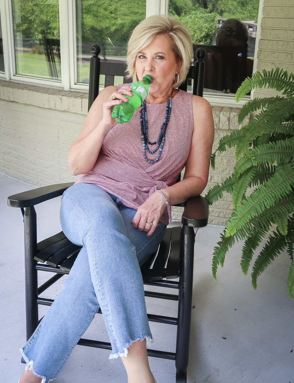 Fashion Blogger 50 Is Not Old is ready for celebrating Labor Day and drinking her Sprite while wearing a red white and blue top twist top, distressed jeans, and Sperry sneakers