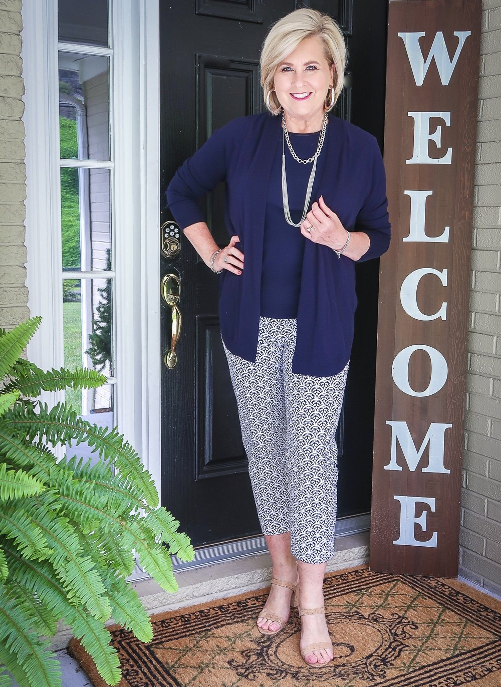 Fashion Blogger 50 Is Not Old is wearing a navy cardigan, a navy tank top, and blue and white ankle pants