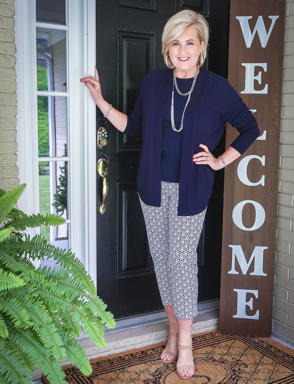 Fashion Blogger 50 Is Not Old is wearing a navy cardigan with a navy tank top and blue and white ankle pants