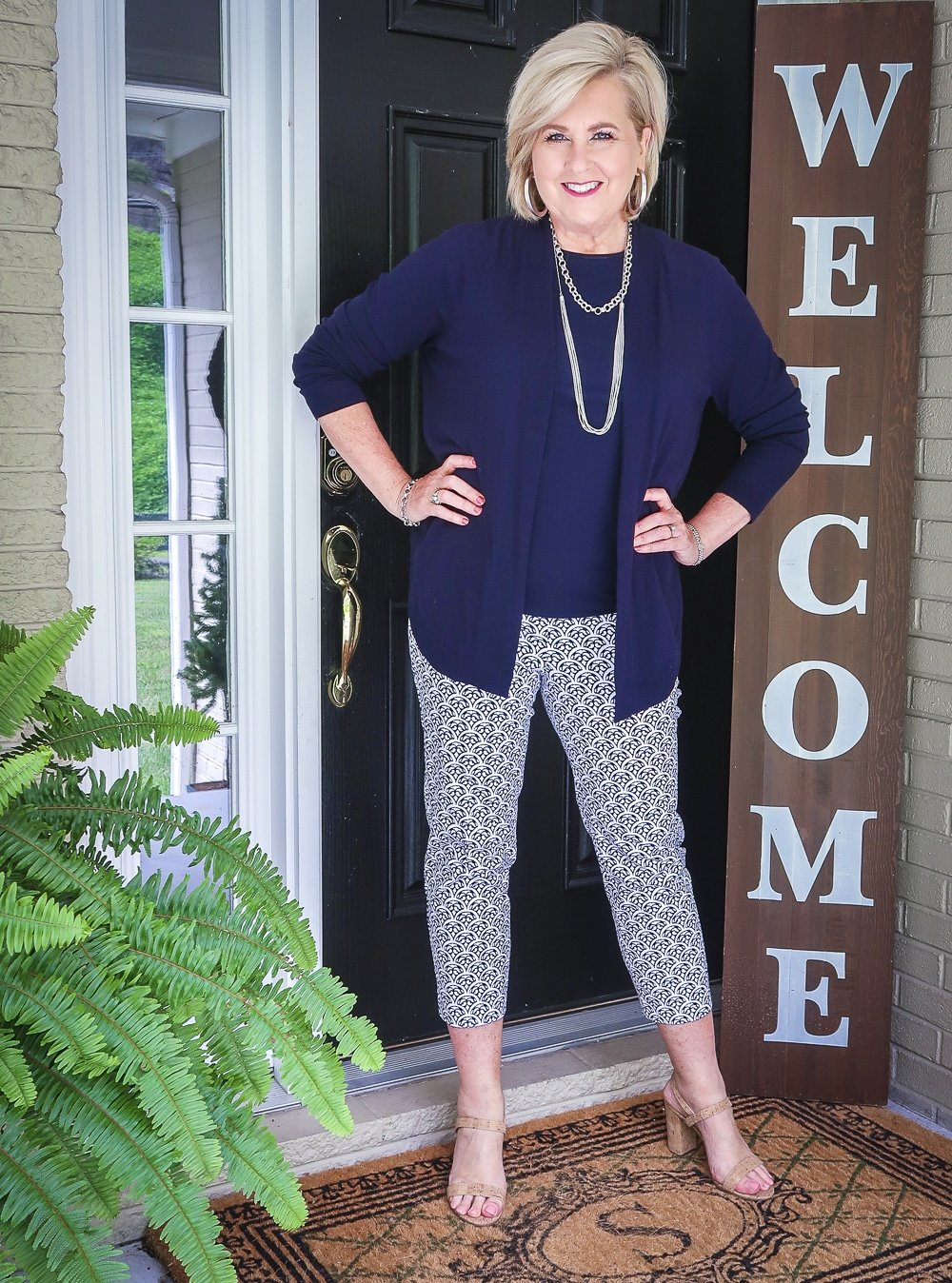 Fashion Blogger 50 Is Not Old is wearing a navy cardigan with a navy tank top, blue and white ankle pants, with cork heels
