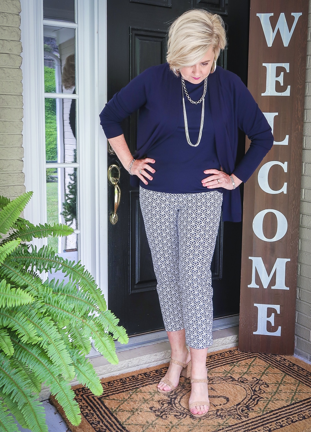 Fashion Blogger 50 Is Not Old is looking down while wearing a navy cardigan with a navy tank top and blue and white ankle pants