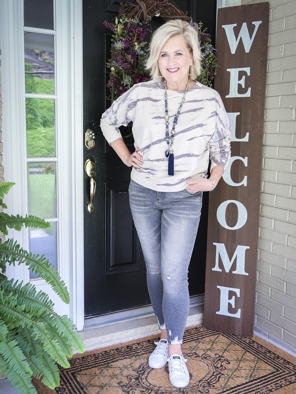 Fashion Blogger 50 Is Not Old is wearing a tie-dye sweatshirt with a pair of washed gray jeans from Kut From The Kloth with Sperry Crest Vibe sneakers