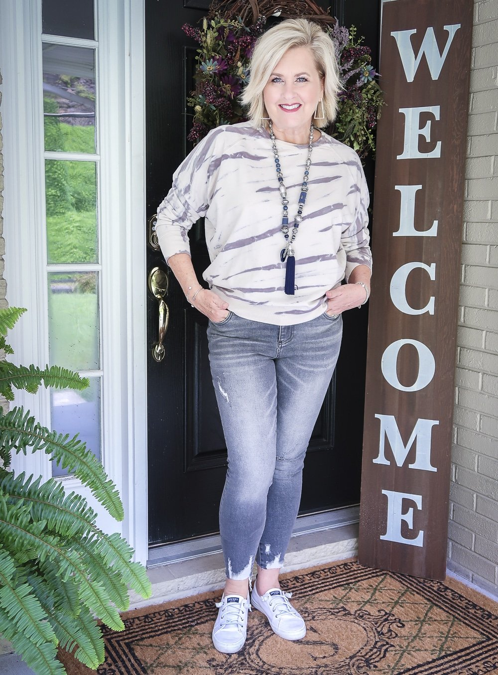 Fashion Blogger 50 Is Not Old is standing with her hands in her pockets and wearing a tie-dye sweatshirt with a pair of washed gray jeans from Kut From The Kloth with Sperry Crest Vibe sneakers