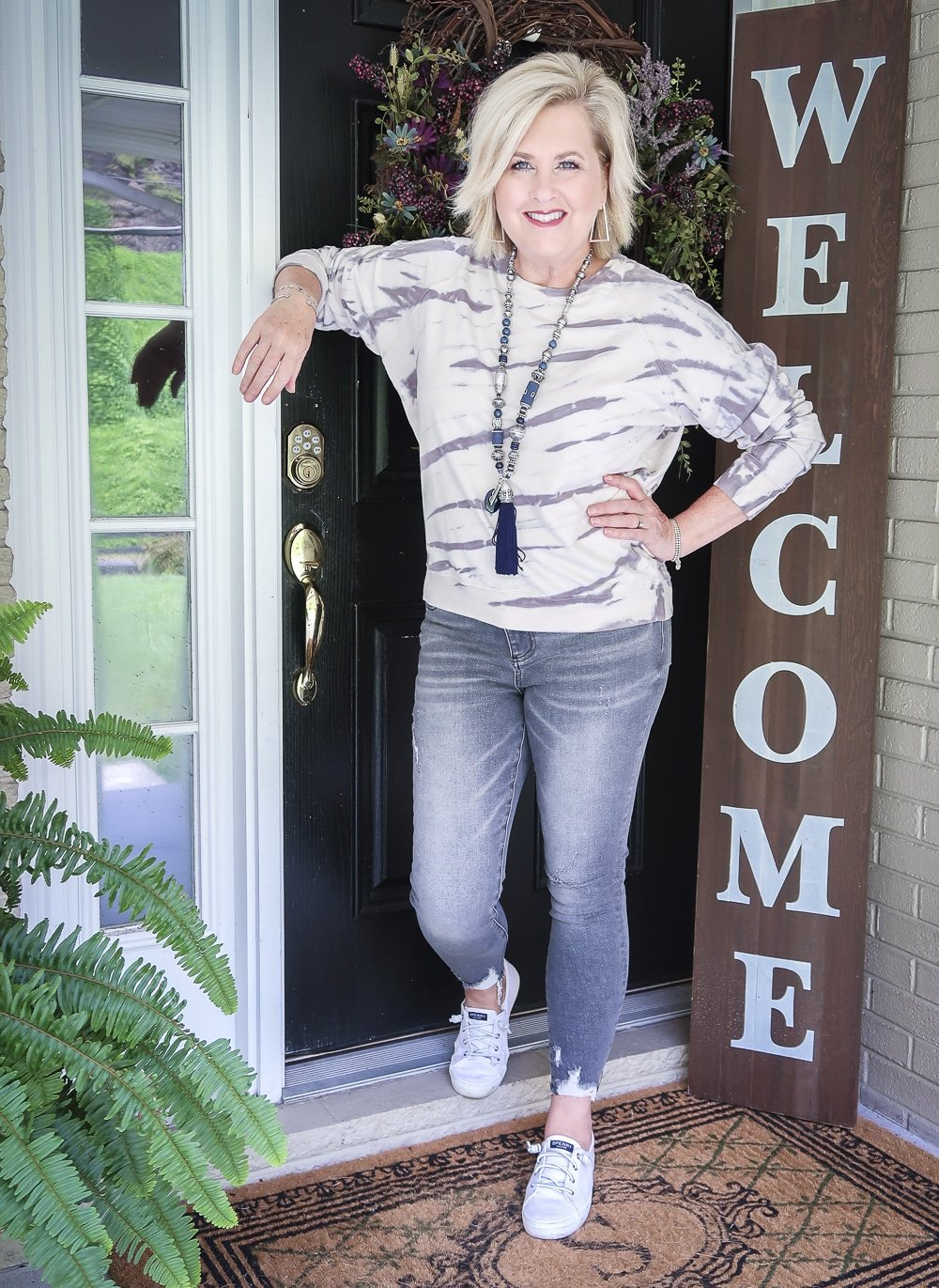 Fashion Blogger 50 Is Not Old is leaning on a door and wearing a tie-dye sweatshirt with a pair of washed gray jeans from Kut From The Kloth with Sperry Crest Vibe sneakers