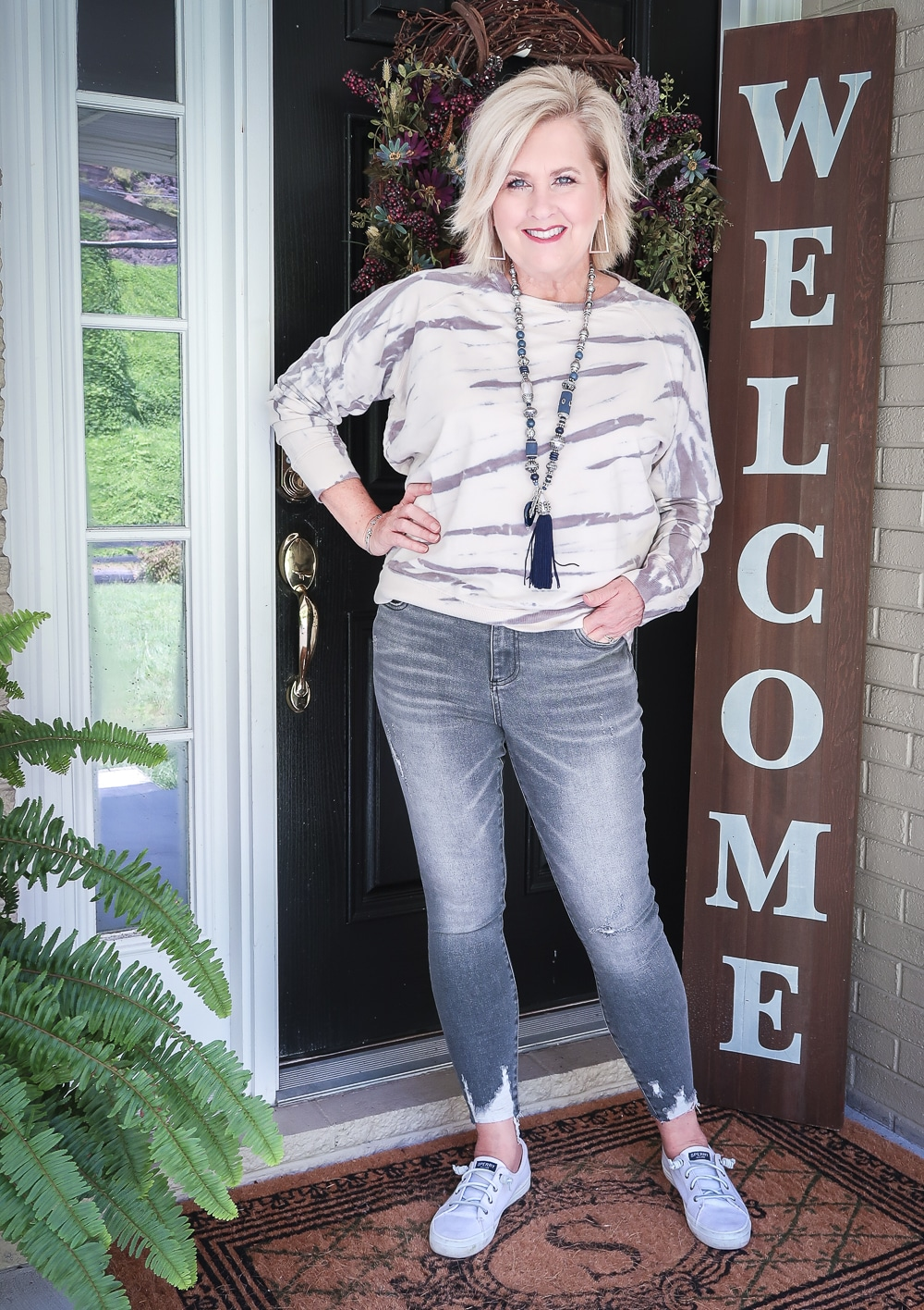 Fashion Blogger 50 Is Not Old is wearing a tie-dye sweatshirt with a pair of washed gray jeans from Kut From The Kloth with Sperry sneakers