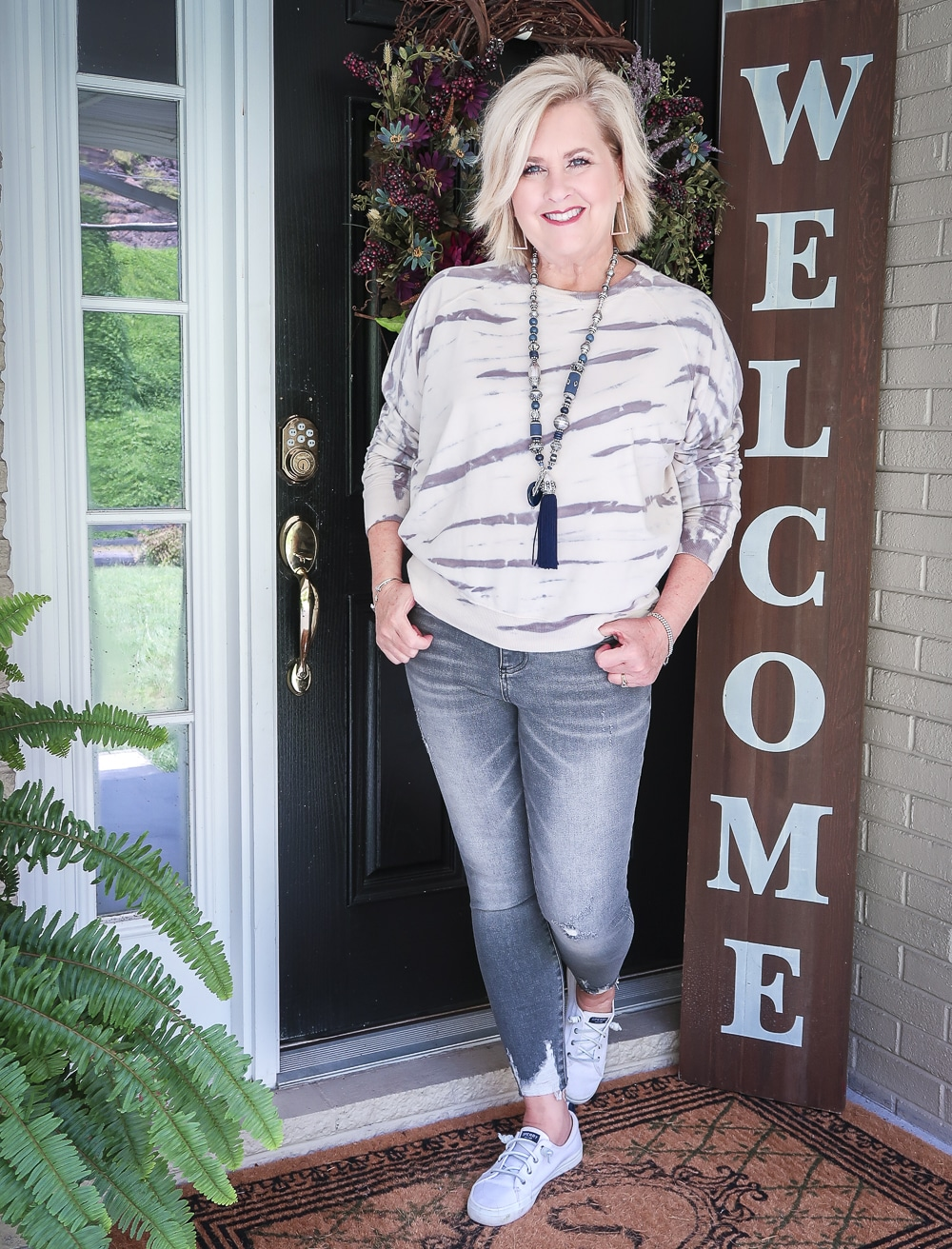 Fashion Blogger 50 Is Not Old is wearing a tie-dye sweatshirt with a pair of washed gray jeans with Sperry Crest Vibe sneakers