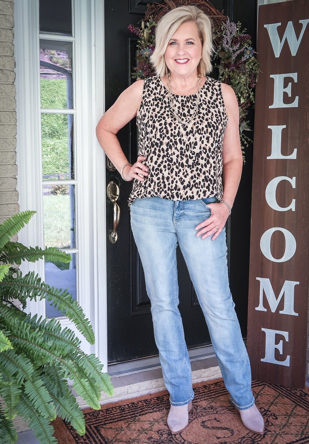 Fashion Blogger 50 Is Not Old is wearing a leopard print top that makes a statement and a pair of straight leg jeans by NYDJ