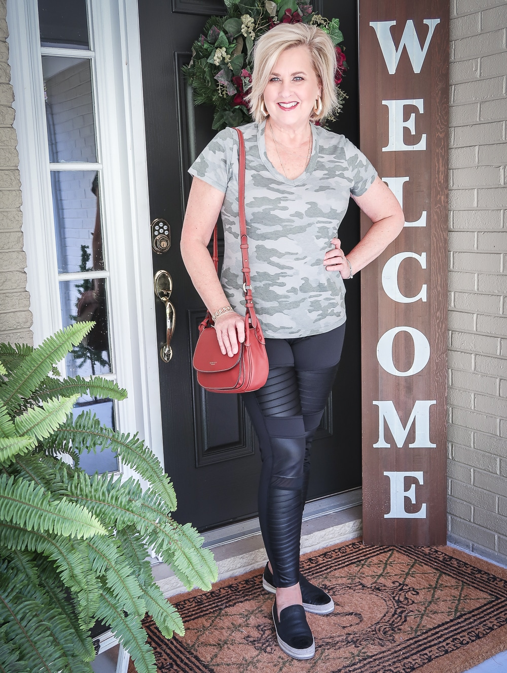 Fashion Blogger 50 Is Not Old is doing a Tuesday Try-On Session with Target and styling a camo v-neck tee shirt, black moto leggings, and a brown crossbody handbag