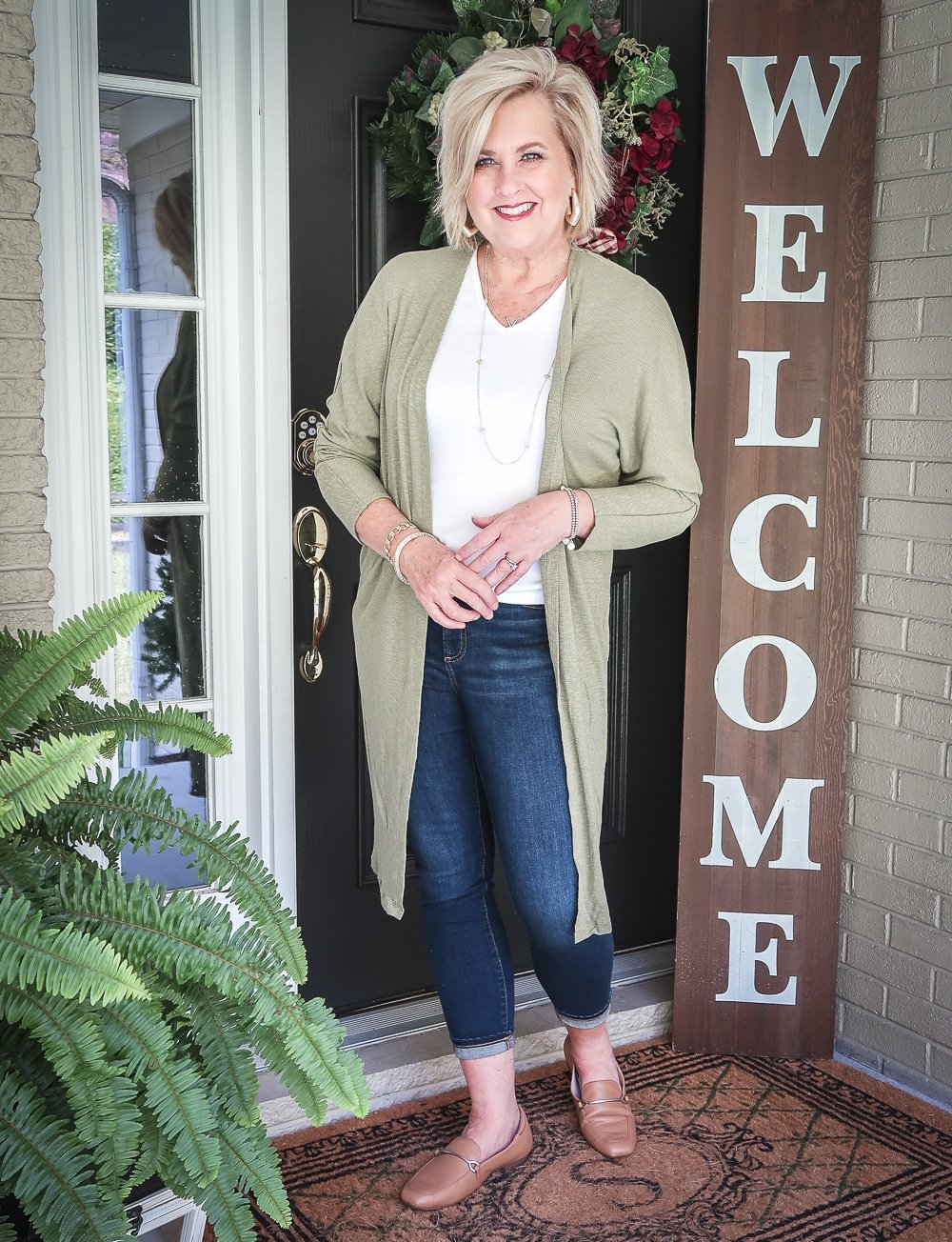 Fashion Blogger 50 Is Not Old is doing a Tuesday Try-On Session with Target and styling a long olive cardigan, a white v-neck tee shirt, and dark jeans from Chico's