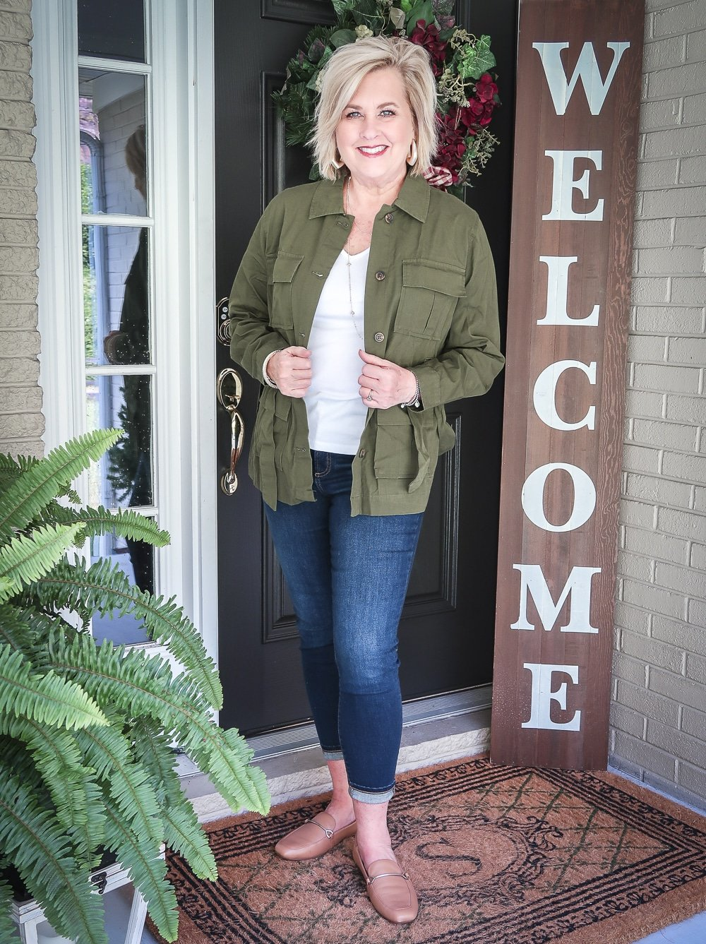 Fashion Blogger 50 Is Not Old is doing a Tuesday Try-On Session with Target and styling a green trucker jacket, a white v-neck tee shirt, and dark jeans from Chico's
