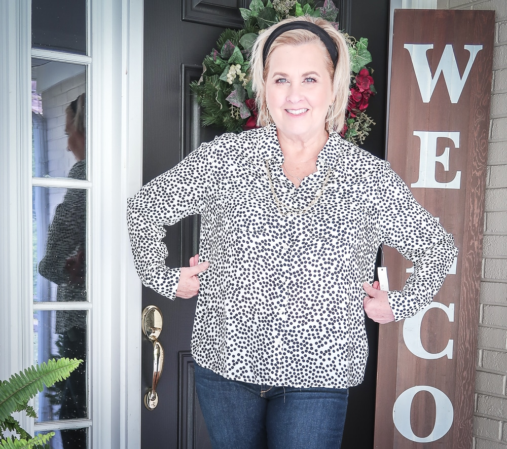 Fashion Blogger 50 Is Not Old has her hair pulled back in a headband, and showing how large a dotted blouse fits