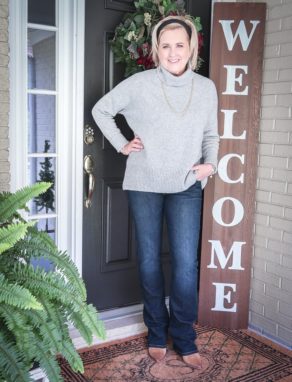 Fashion Blogger 50 Is Not Old is wearing a chunky sweater, bootcut jeans, and ankle boots for fall