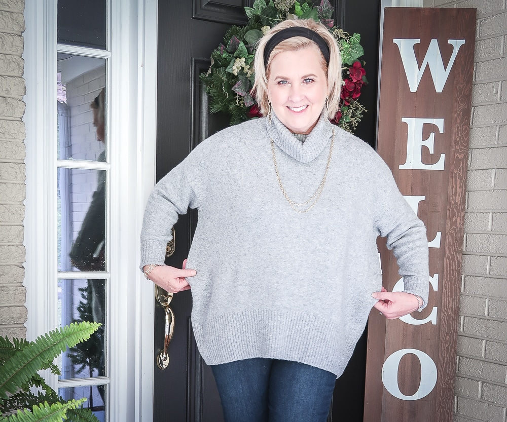 Fashion Blogger 50 Is Not Old has her hair pulled back in a headband, and is wearing a chunky sweater that is too big