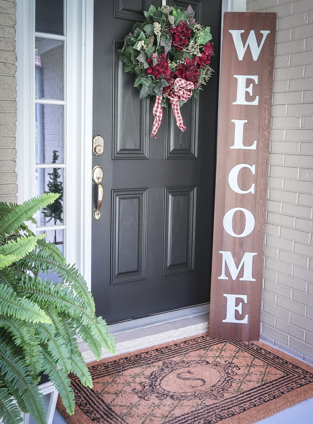Fashion Blogger 50 Is Not Old is showing a black front door with a wreath and a Welcome sign