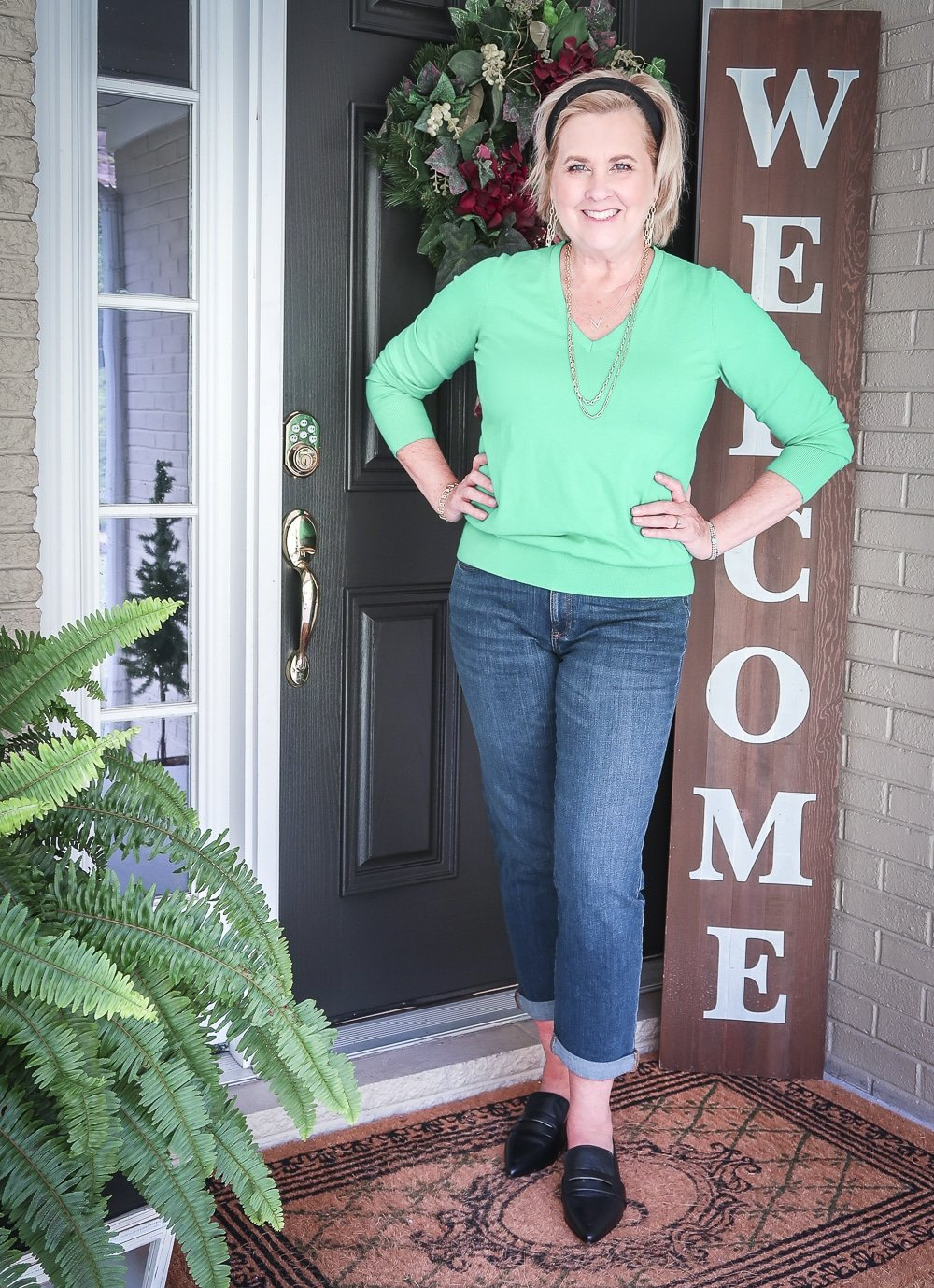 Fashion Blogger 50 Is Not Old is wearing an emerald green sweater, girlfriend jeans, and pointed-toe loafers