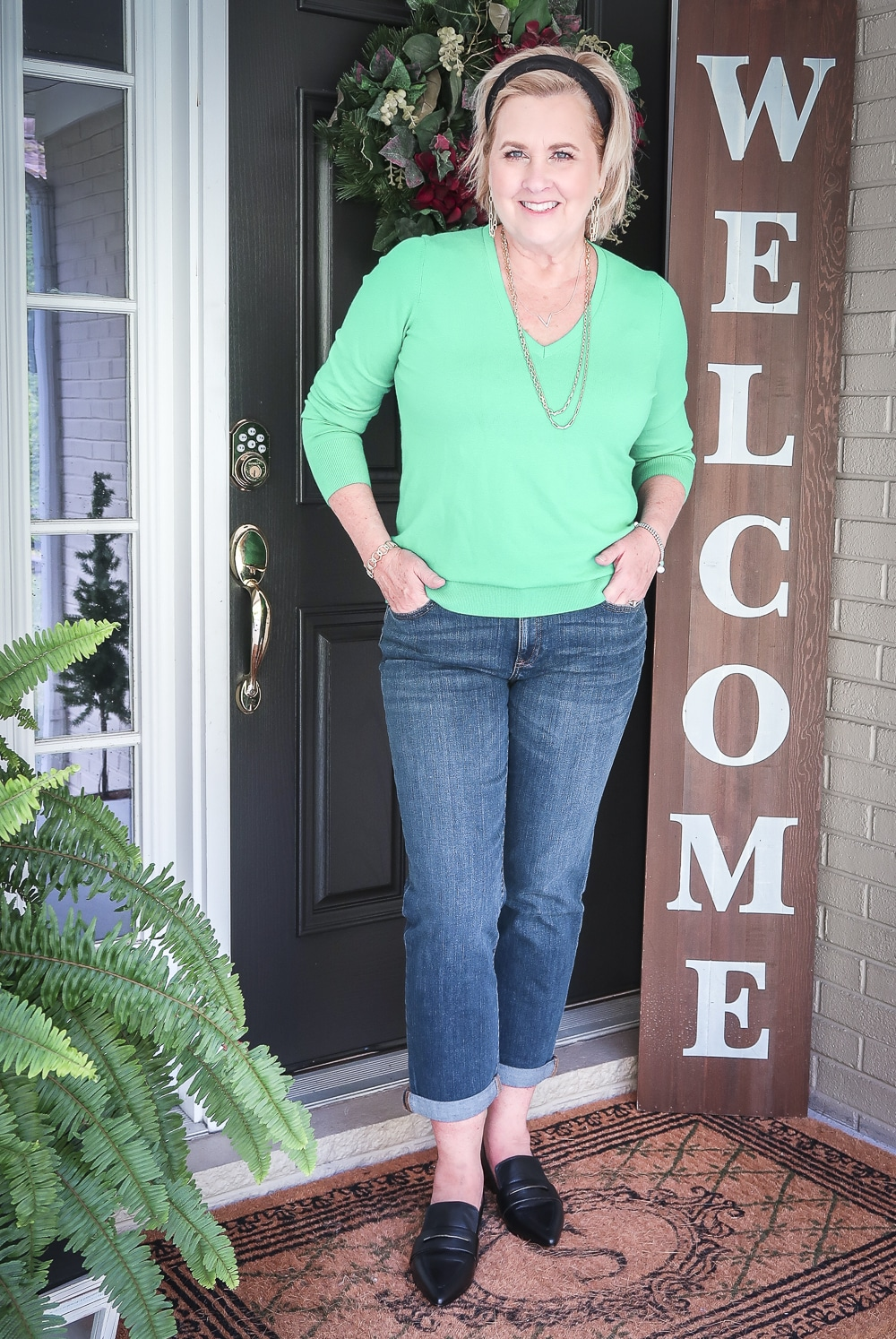 Fashion Blogger 50 Is Not Old is wearing a vibrant green v-neck sweater, girlfriend crop jeans, and black pointy loafers