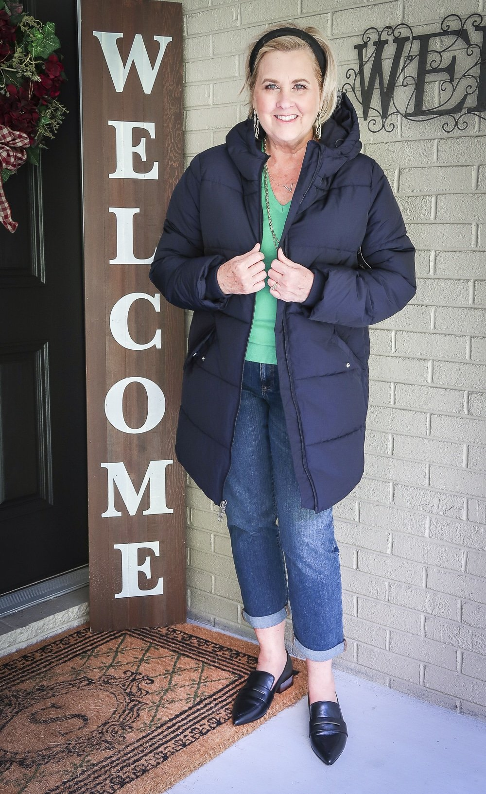 Fashion Blogger 50 Is Not Old is wearing a vibrant green v-neck sweater with a navy puffer coat, girlfriend crop jeans, and black pointy loafers