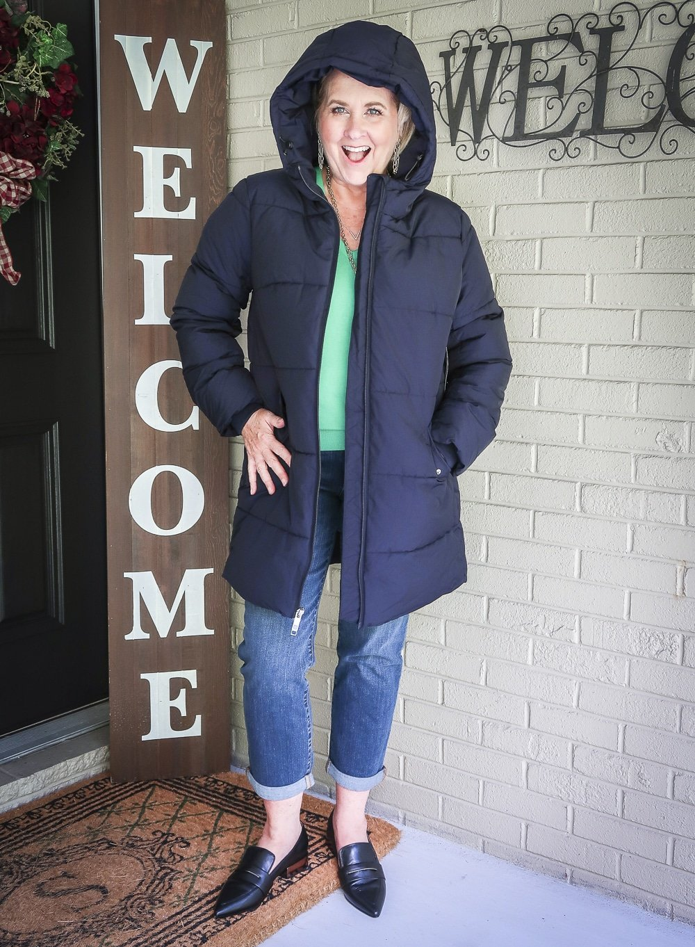 Fashion Blogger 50 Is Not Old is wearing a navy puffer coat, girlfriend crop jeans, and black pointy loafers