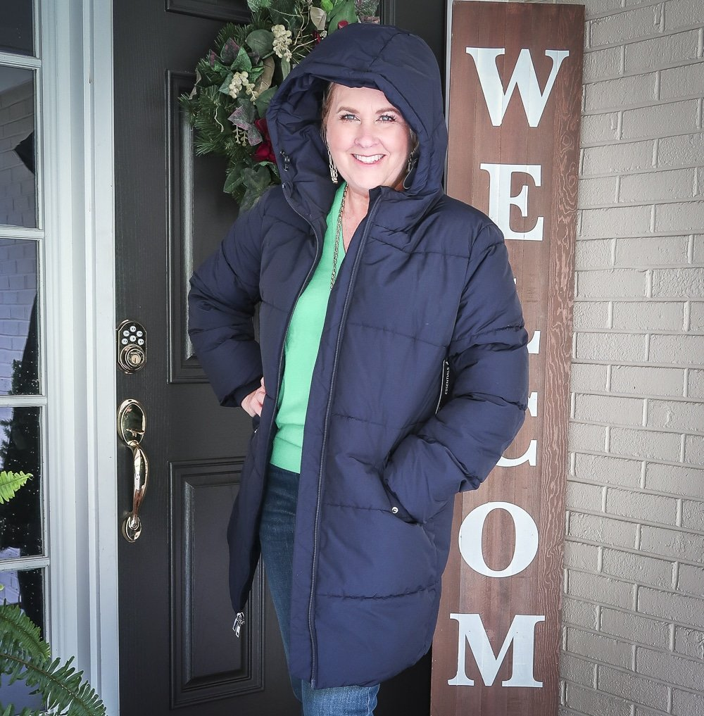 Fashion Blogger 50 Is Not Old is wearing a vibrant green v-neck sweater with a navy puffer coat