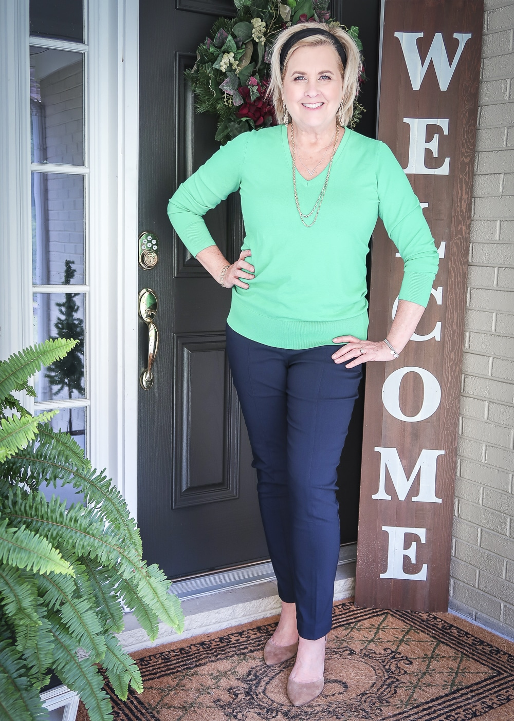Fashion Blogger 50 Is Not Old is wearing an Emerald green sweater, navy dress pants, and neutral heels