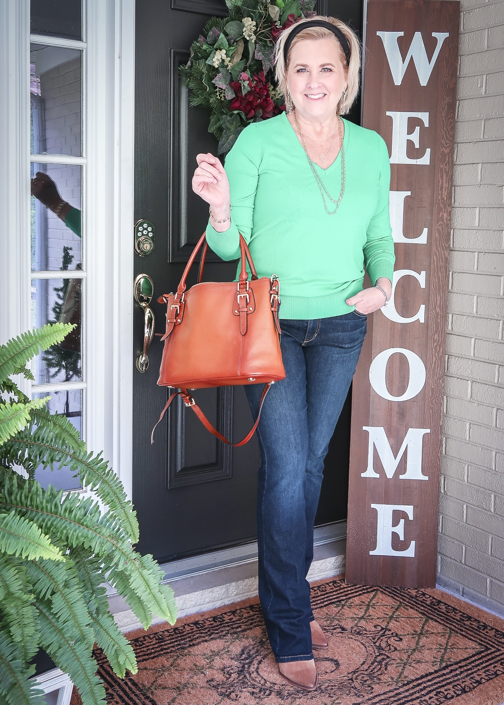 Fashion Blogger 50 Is Not Old is wearing a vibrant green sweater, bootcut jeans, ankle boots, and carrying a leather handbag for fall