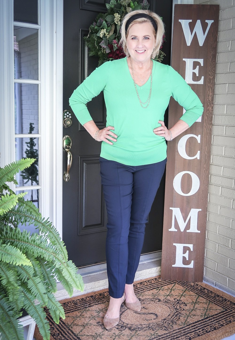 Fashion Blogger 50 Is Not Old is wearing a vibrant green v-neck sweater and navy pants