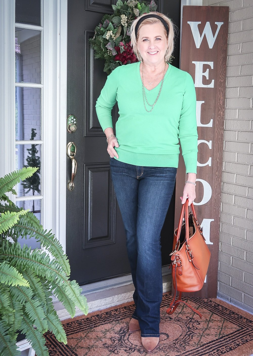 Fashion Blogger 50 Is Not Old is wearing a vibrant green sweater, bootcut jeans, and ankle boots for fall
