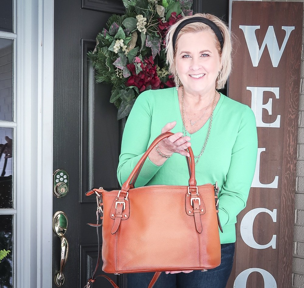 Fashion Blogger 50 Is Not Old is wearing a vibrant green sweater and showing a brown leather handbag