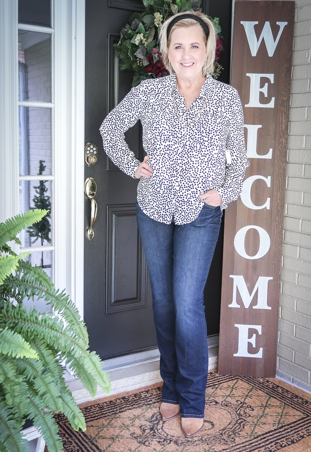 Fashion Blogger 50 Is Not Old is wearing a dotted blouse, bootcut jeans, and ankle boots for fall