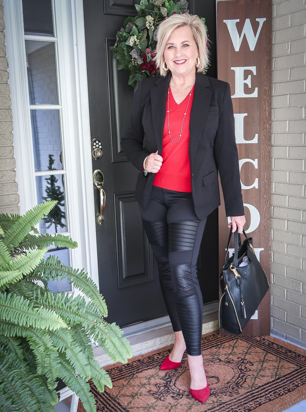 Fashion Blogger 50 Is Not Old is looking modern and edgy in this pair of black moto leggings and a red sweater and red pumps
