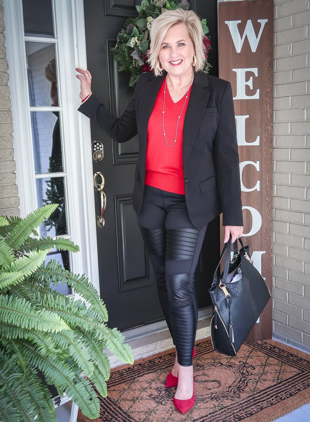 Fashion Blogger 50 Is Not Old is looking classy in this pair of black faux leather moto leggings and a red sweater and red pumps