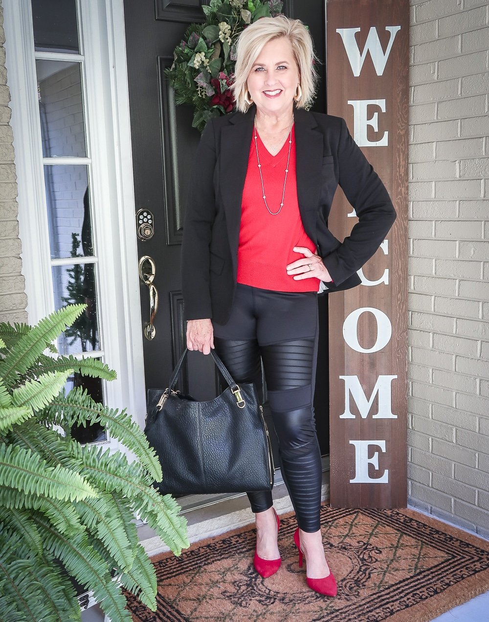 Fashion Blogger 50 Is Not Old is looking modern and edgy in this pair of black faux leather moto leggings, red v-neck sweater and red pumps
