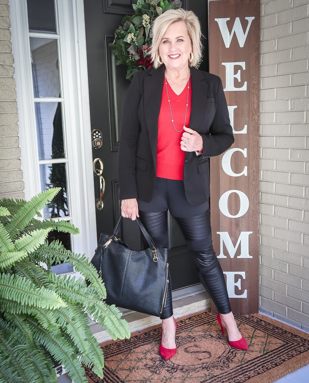 Fashion Blogger 50 Is Not Old is looking modern and edgy in this pair of black faux leather moto leggings and a red sweater and red pumps