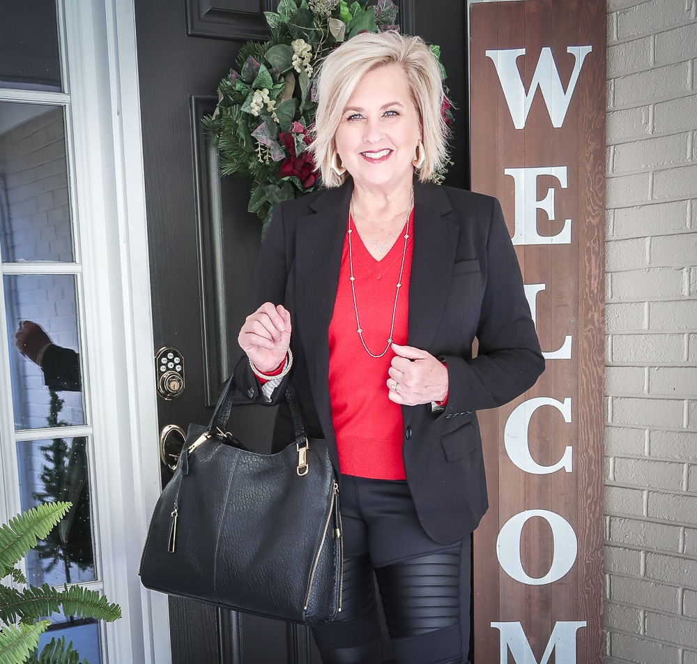 Fashion Blogger 50 Is Not Old is looking modern and edgy in this pair of black faux leather moto leggings and a red sweater, red pumps, and a black handbag