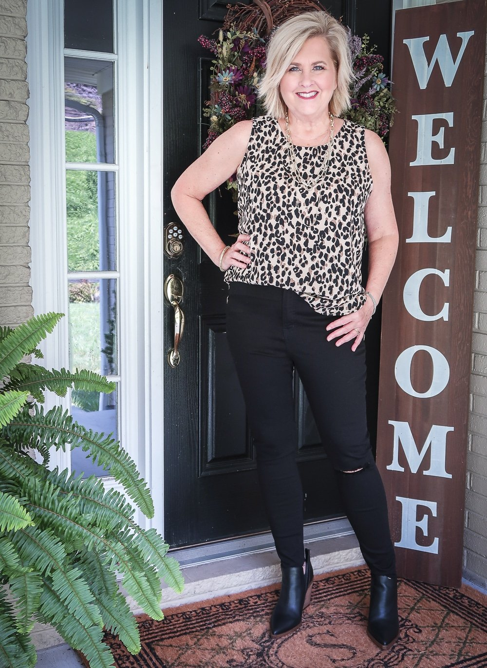 Fashion Blogger 50 Is Not Old is wearing a leopard print top that makes a statement and a pair of black distressed jeans by Madewell
