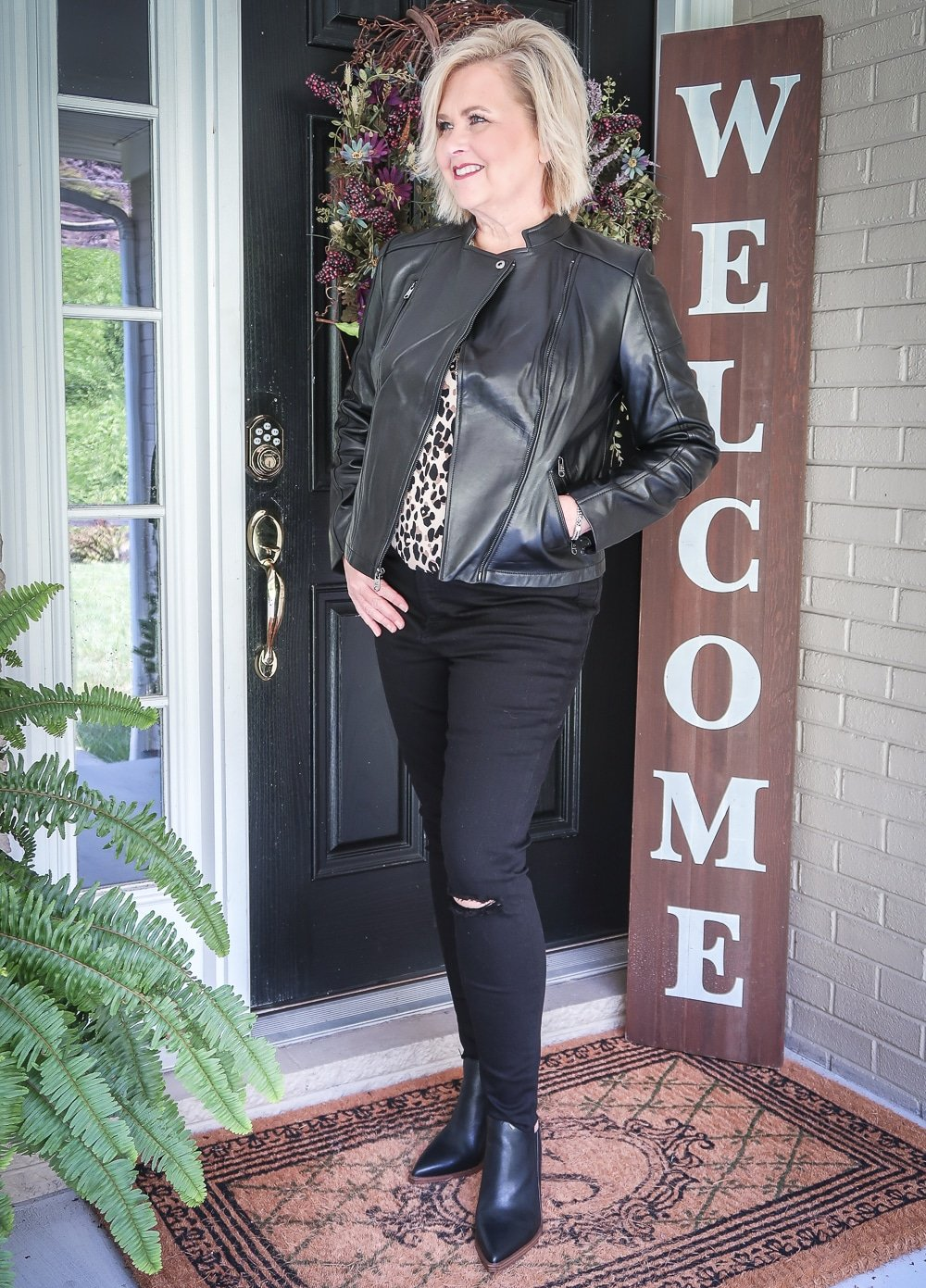 Fashion Blogger 50 Is Not Old is wearing a leopard print statement top, a black moto jacket, and a pair of black distressed jeans by Madewell