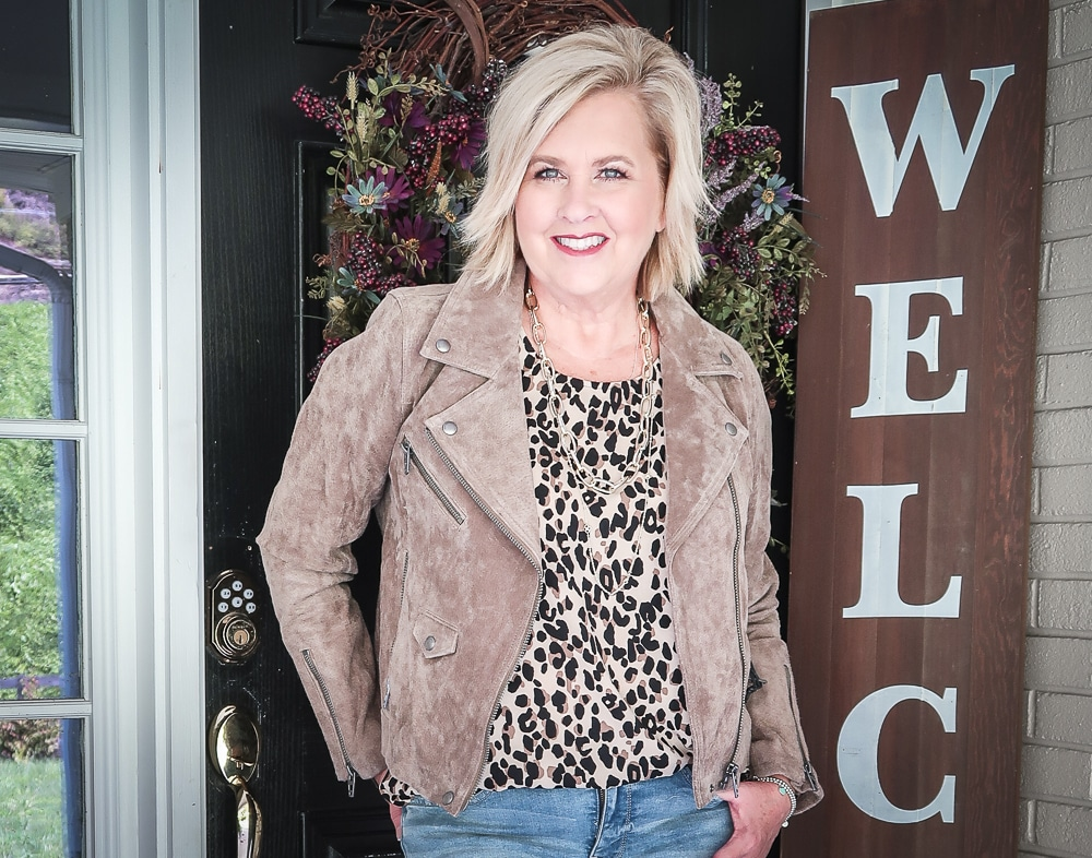 Fashion Blogger 50 Is Not Old is wearing a leopard print statement top and a taupe suede moto jacket