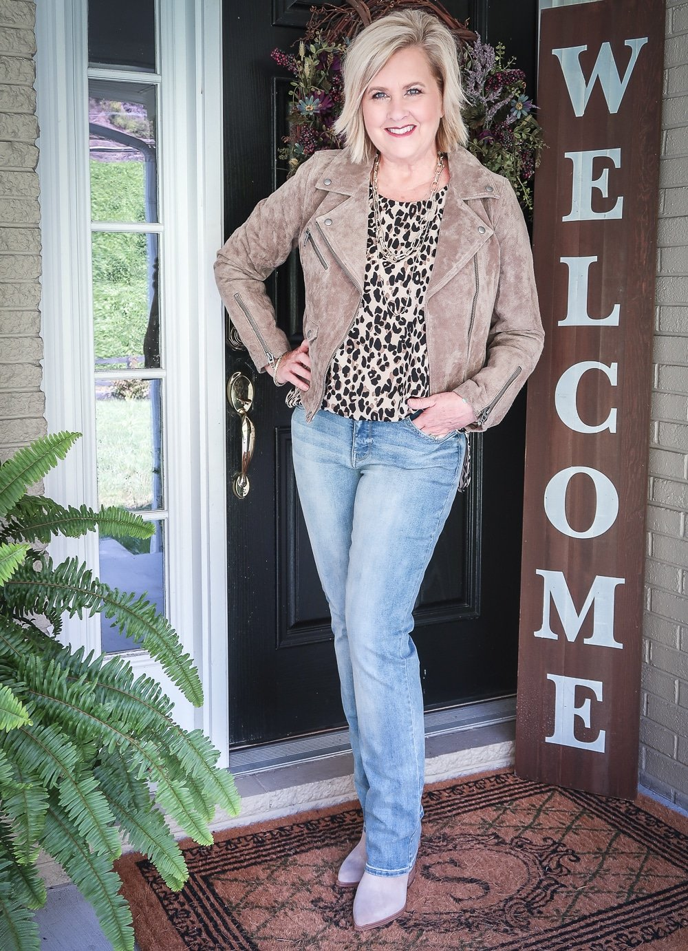 Fashion Blogger 50 Is Not Old is wearing a leopard print statement top, a taupe suede moto jacket, and a pair of straight leg jeans
