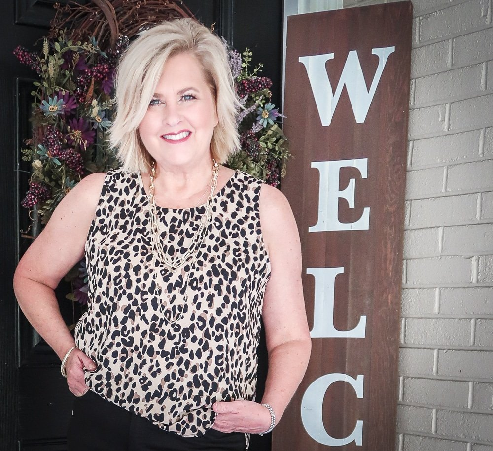 Fashion Blogger 50 Is Not Old is wearing a leopard print statement top and gold jewelry from Kendra Scott