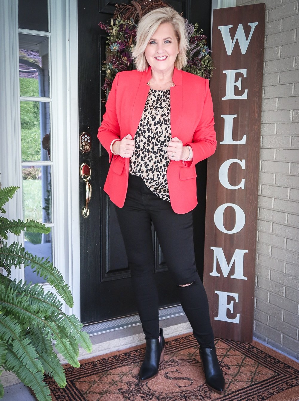 Fashion Blogger 50 Is Not Old is wearing a leopard print statement top, a red blazer, and a pair of black distressed jeans by Madewell