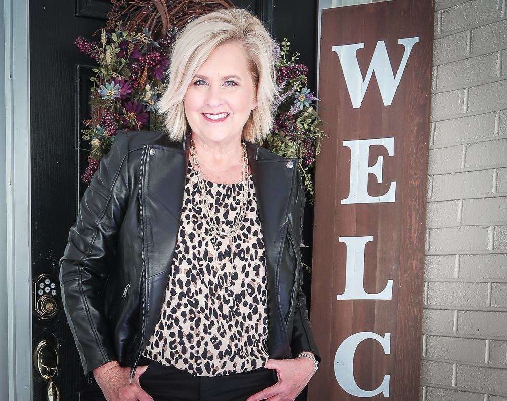 Fashion Blogger 50 Is Not Old is wearing a leopard print statement top and a black lambskin moto jacket