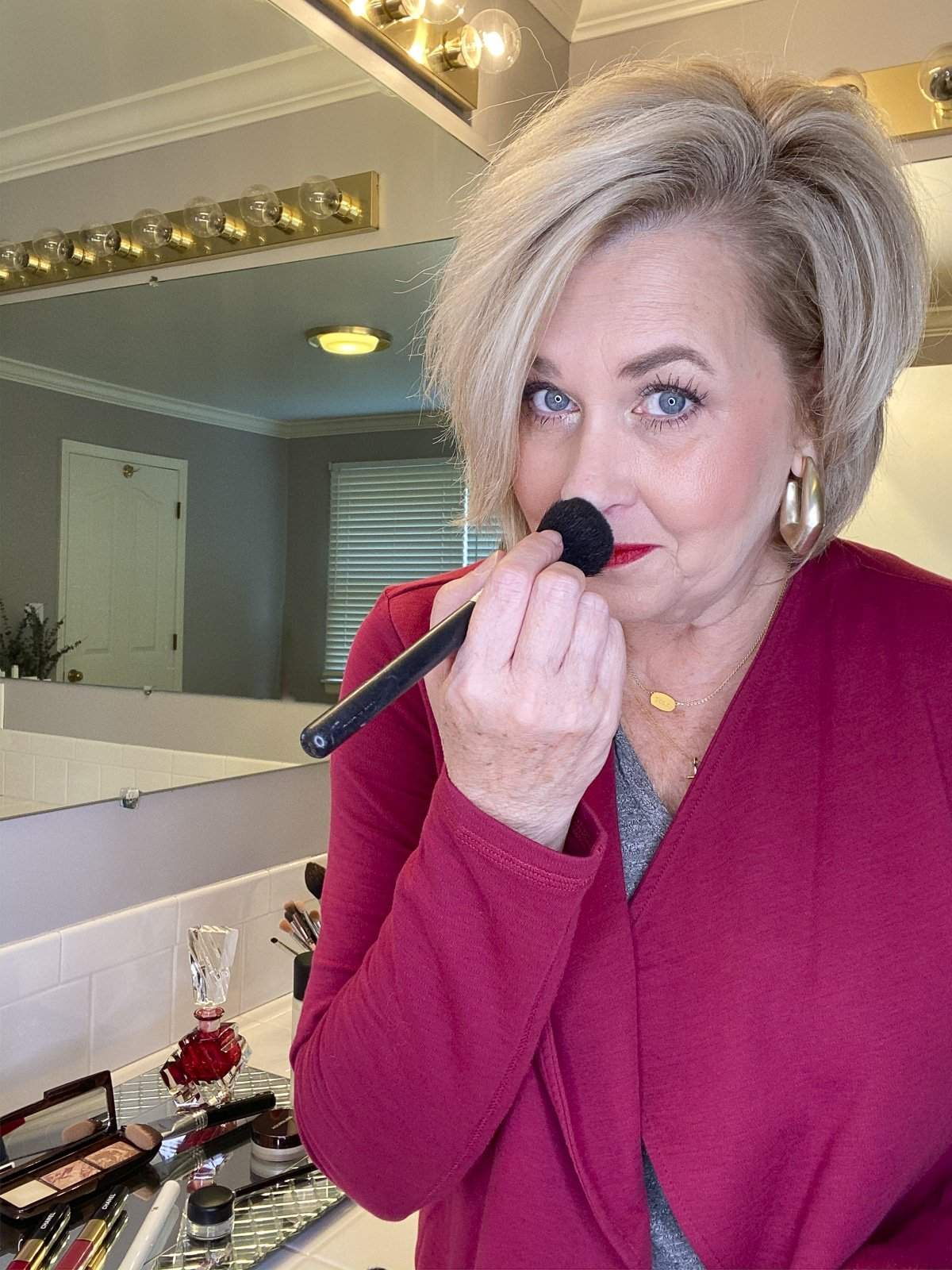 Fashion Blogger 50 Is Not Old powdering her nose with makeup purchased from Nordstrom