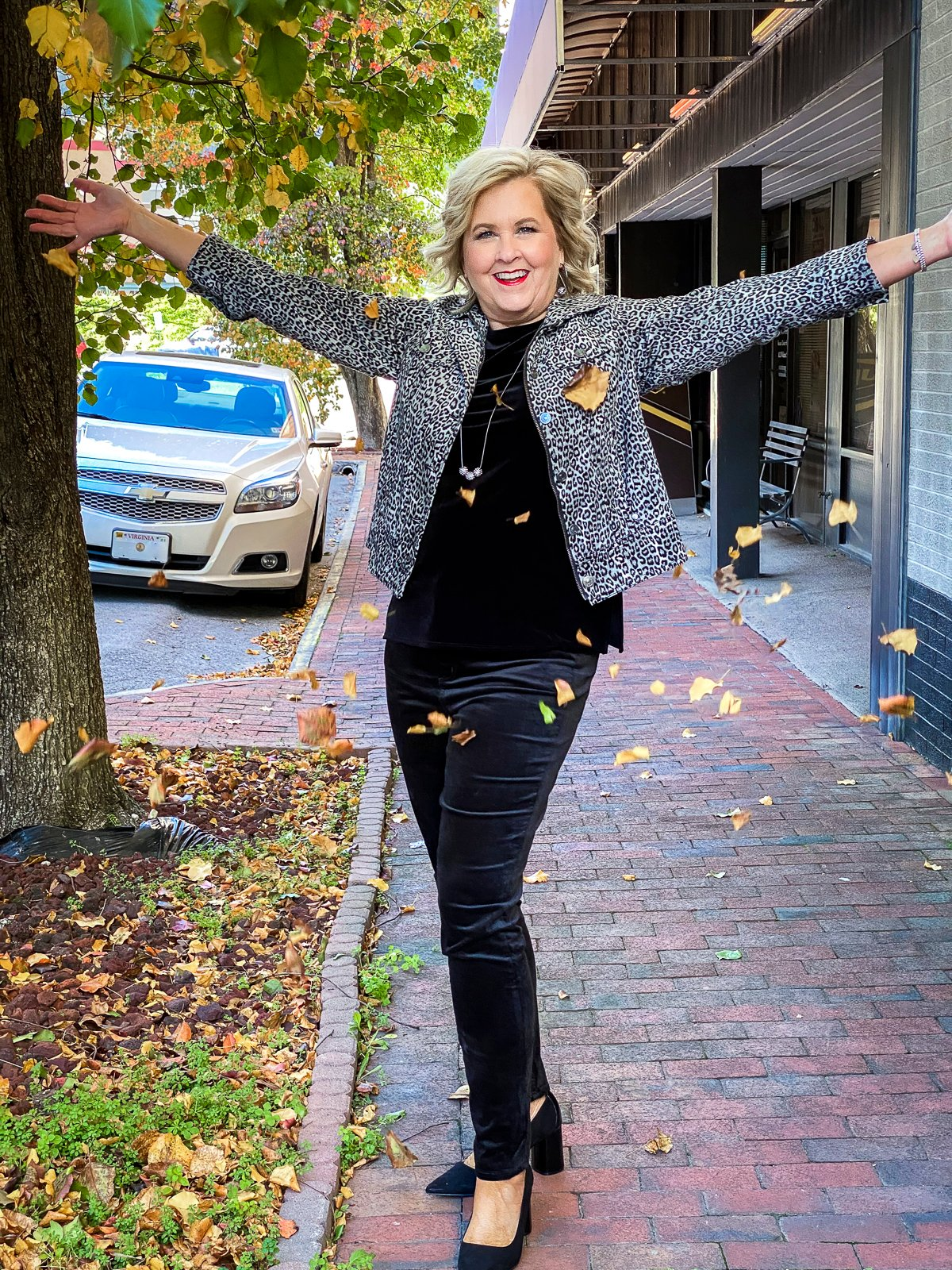 Fashion Blogger 50 Is Not Old is showered with leaves in a black velvet tank top, an animal print jacket, and black velvet jeggings from Chico's