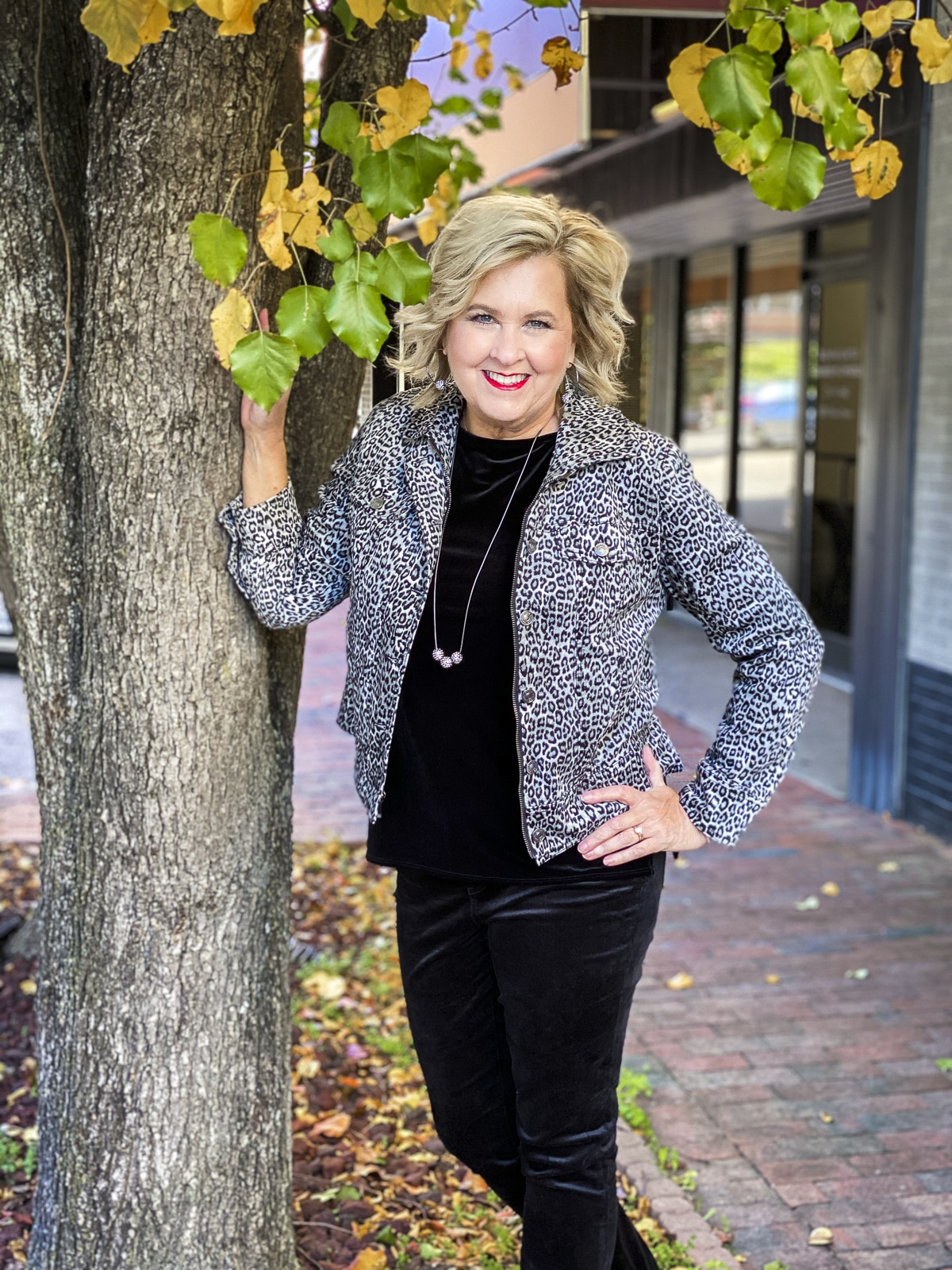 Fashion Blogger 50 Is Not Old is festive under a tree with fall leaves in a black velvet tank top and jeggings from Chico's