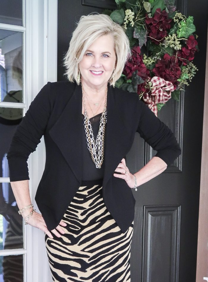 Fashion Blogger 50 Is Not Old is wearing an animal print sweater skirt with a black camisole and blazer
