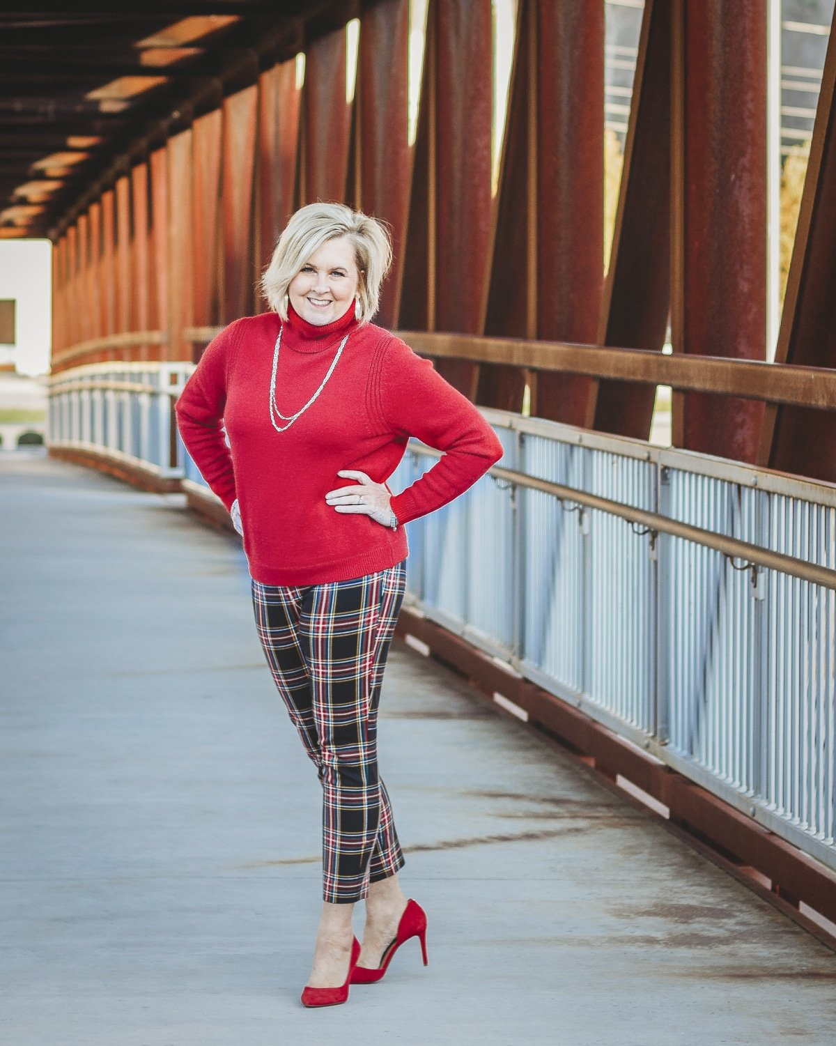 Fashion Blogger 50 Is Not Old is looking festive in this red turtleneck sweater, gold jewelry, plaid pants, and red heels