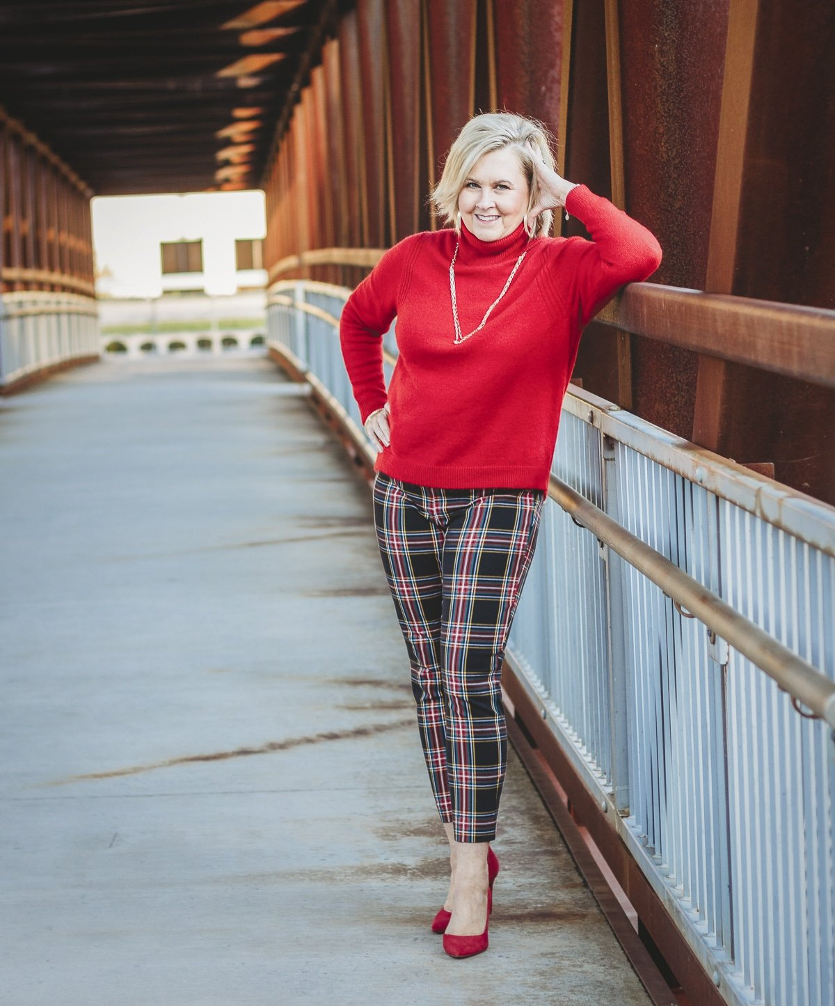 Fashion Blogger 50 Is Not Old is looking festive in this red turtleneck sweater and plaid pants with red pump heels